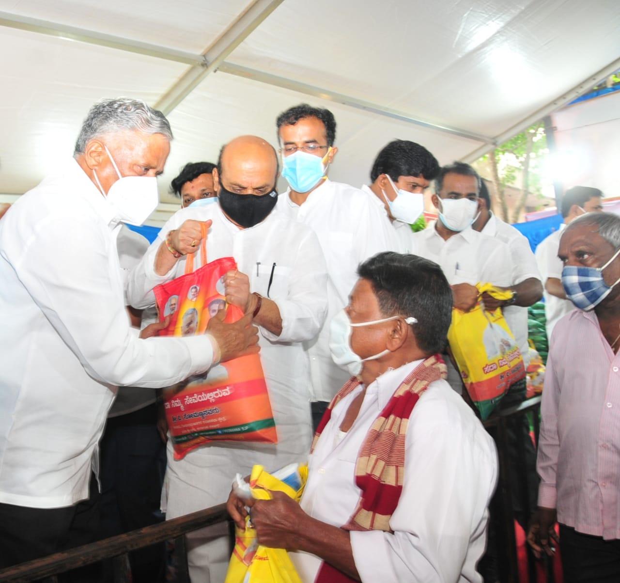 Karnataka Minister V Somanna distributes food grains with Home Minister Basavaraj Bommai